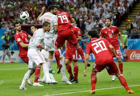 Spain's Diego Costa, center left, fails to head the ball under pressure from Iran's Majid Hosseini, centre right, during the group B match between Iran and Spain at the 2018 soccer World Cup in the Kazan Arena in Kazan, Russia