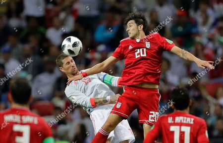 Spain's Sergio Ramos, left, heads the ball under pressure from Iran's Mehdi Torabi during the group B match between Iran and Spain at the 2018 soccer World Cup in the Kazan Arena in Kazan, Russia