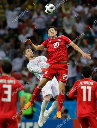 Spain's Sergio Ramos, left, goes to head the ball under pressure from Iran's Mehdi Torabi during the group B match between Iran and Spain at the 2018 soccer World Cup in the Kazan Arena in Kazan, Russia