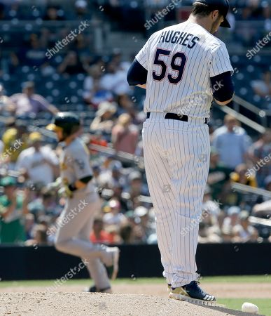 Stock Image of San Diego Padres relief pitcher Phil Hughes, right, waits while Oakland Athletics' Jed Lowrie circles the bases after hitting a two-run home run during the eighth inning of a baseball game in San Diego