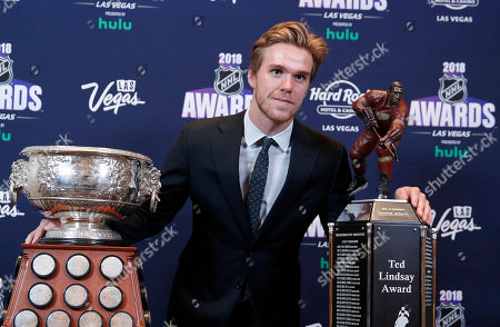 Edmonton Oilers' Connor McDavid poses with the Art Ross Trophy, left, and the Ted Lindsay Award at the NHL Awards, in Las Vegas