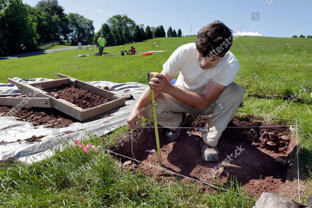 Paul Brown, of the Public Archaeology Facility at Binghamton University, measures a dig at the site of the original Woodstock Music and Art Fair, in Bethel, N.Y. The main mission of Binghamton University's Public Archaeology Facility is to help map out more exactly where The Who, Creedence Clearwater Revival, Janis Joplin and Joe Cocker wowed the crowds 49 years ago