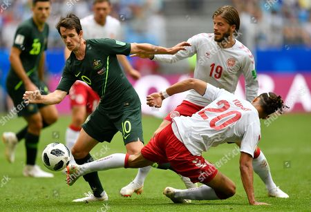 Australia's Robbie Kruse, left, is challenged by Denmark's Yussuf Yurary Poulsen, front, and Lasse Schone during the group C match between Denmark and Australia at the 2018 soccer World Cup in the Samara Arena in Samara, Russia