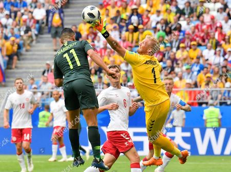 Denmark goalkeeper Kasper Schmeichel, right, deflects a ball ahead of Australia's Andrew Nabbout, left, as Denmark's Andreas Christensen looks on during the group C match between Denmark and Australia at the 2018 soccer World Cup in the Samara Arena in Samara, Russia
