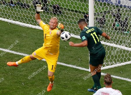 Denmark goalkeeper Kasper Schmeichel, left, and Australia's Andrew Nabbout challenge for the ball during the group C match between Denmark and Australia at the 2018 soccer World Cup in the Samara Arena in Samara, Russia