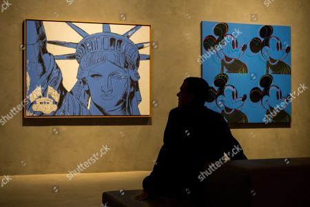 A woman looks at some works shown at the exhibition 'Still Blue' in Barcelona, Spain, 21 June 2018. The exhibition shows work of Andy Warhol, Jean Michel Basquiat, Mark Tansey, Lucio Fontana, Yves Klein, Howard Hodgkin, Penck and Joerg Immendorf. The display will be shown from 21 June to 04 November 2018.
