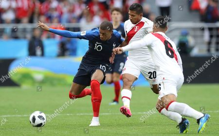 France's Kylian Mbappe, left vies for the ball with Peru's Alberto Rodriguez during the group C match between France and Peru at the 2018 soccer World Cup in the Yekaterinburg Arena in Yekaterinburg, Russia