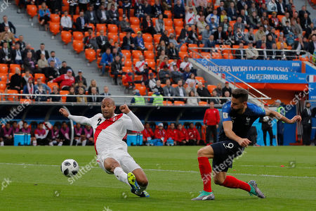 Peru's Alberto Rodriguez, left, tries to block a shoot by France's Olivier Giroud during the group C match between France and Peru at the 2018 soccer World Cup in the Yekaterinburg Arena in Yekaterinburg, Russia