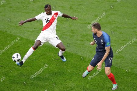 Peru's Christian Ramos, left, and France's Olivier Giroud challenge for the ball during the group C match between France and Peru at the 2018 soccer World Cup in the Yekaterinburg Arena in Yekaterinburg, Russia