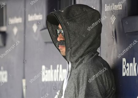 Stock Image of Ichiro Suzuki, special assistant to the chairman of the Seattle Mariners, wears a fake mustache and a hoodie as he sits in the dugout and watches the New York Yankees bat during the first inning of a baseball game, at Yankee Stadium in New York. Suzuki donned a Bobby Valentine-style disguise and sneaked into the Seattle dugout to watch a bit of the action at Yankee Stadium