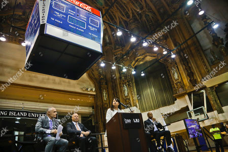 Barclays Center CEO Brett Yormark, far left, Long Island University (LIU) Board Chairman Erick Krasnoff, second from left, and Brooklyn Borough President Eric Adams, far right, listen as LIU President Kimberly Cline, second from right, speak before the lowering of a scoreboard from the ornate ceiling at the old Paramount Theatre at LIU's Brooklyn campus, during kick-off ceremony for a renovation project, in New York. The Paramount, which opened its doors in 1928 as a movie palace and later converted into a gymnasium in the 1960s for LIU Blackbirds basketball, is set to undergo a two-year renovation into a cutting edge entertainment arts venue, while keeping its original decor intact