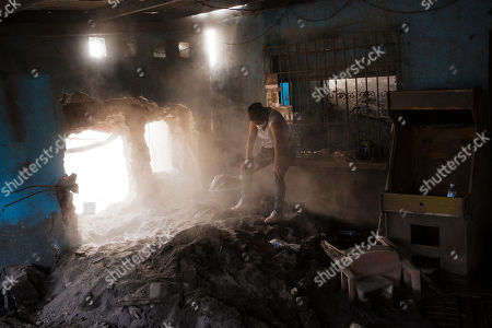 """Angelica Maria Alvarez rests, exhausted inside her home destroyed by the eruption of the the Volcan de Fuego or """"Volcano of Fire,"""" in San Miguel Los Lotes, Guatemala. Alvarez is still searching for the remains of more than 10 family members, including her husband and two daughters"""
