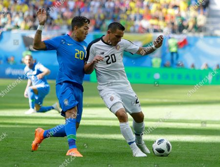 Stock Picture of Brazil's Roberto Firmino, left, and Costa Rica's David Guzman right, battle for the ball during the group E match between Brazil and Costa Rica at the 2018 soccer World Cup in the St. Petersburg Stadium in St. Petersburg, Russia