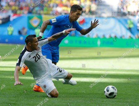 Stock Image of Costa Rica's David Guzman, left, falls as Brazil's Roberto Firmino takes the ball during the group E match between Brazil and Costa Rica at the 2018 soccer World Cup in the St. Petersburg Stadium in St. Petersburg, Russia