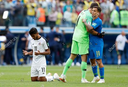 Costa Rica's Johan Venegas, left, reacts as Brazil goalkeeper Alisson and teammate Philippe Coutinho, right, embrace after their group E match between Brazil and Costa Rica at the 2018 soccer World Cup in the St. Petersburg Stadium in St. Petersburg, Russia