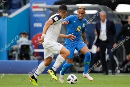 Brazil's Neymar, right, and Costa Rica's Johnny Acosta challenge for the ball during the group E match between Brazil and Costa Rica at the 2018 soccer World Cup in the St. Petersburg Stadium in St. Petersburg, Russia