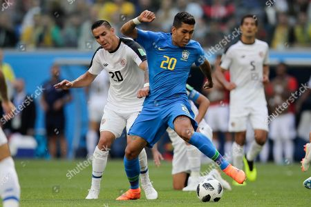 Brazil's Roberto Firmino, right, and Costa Rica's David Guzman challenge for the ball during the group E match between Brazil and Costa Rica at the 2018 soccer World Cup in the St. Petersburg Stadium in St. Petersburg, Russia