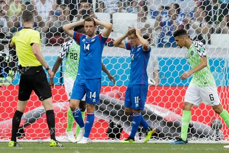 Iceland's Kari Arnason, second left, and Iceland's Alfred Finnbogason, second right, react during the group D match between Nigeria and Iceland at the 2018 soccer World Cup in the Volgograd Arena in Volgograd, Russia