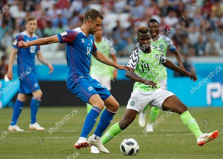 Kari Arnason (L) of Iceland and Kelechi Iheanacho of Nigeria in action during the FIFA World Cup 2018 group D preliminary round soccer match between Nigeria and Iceland in Volgograd, Russia, 22 June 2018. (RESTRICTIONS APPLY: Editorial Use Only, not used in association with any commercial entity - Images must not be used in any form of alert service or push service of any kind including via mobile alert services, downloads to mobile devices or MMS messaging - Images must appear as still images and must not emulate match action video footage - No alteration is made to, and no text or image is superimposed over, any published image which: (a) intentionally obscures or removes a sponsor identification image; or (b) adds or overlays the commercial identification of any third party which is not officially associated with the FIFA World Cup)