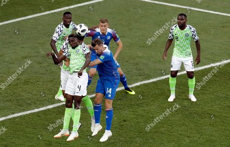 Iceland's Kari Arnason, center, is airborne with Nigeria's Onyinye Ndidi during the group D match between Nigeria and Iceland at the 2018 soccer World Cup in the Volgograd Arena in Volgograd, Russia