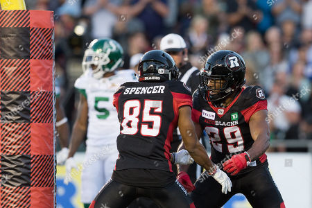 Ottawa Redblacks William Powell (29) celebrates with Diontae Spencer (85) after scoring a touchdown during the CFL game between the Saskatchewan Roughriders and Ottawa Redblacks at TD Place Stadium in Ottawa, Canada