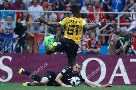 Michy Batshuayi, Farouk Ben Mustapha. Belgium's Michy Batshuayi, top, moves the ball past Tunisia goalkeeper Farouk Ben Mustapha during the group G match between Belgium and Tunisia at the 2018 soccer World Cup in the Spartak Stadium in Moscow, Russia