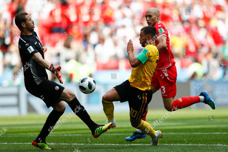 Belgium's Eden Hazard, center, challenges for the ball with Tunisia goalkeeper Farouk Ben Mustapha before scoring his side's fourth goal during the group G match between Belgium and Tunisia at the 2018 soccer World Cup in the Spartak Stadium in Moscow, Russia