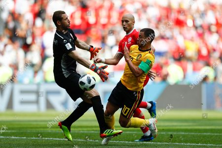 Belgium's Eden Hazard, right, challenges for the ball with Tunisia goalkeeper Farouk Ben Mustapha before scoring his side's fourth goal during the group G match between Belgium and Tunisia at the 2018 soccer World Cup in the Spartak Stadium in Moscow, Russia