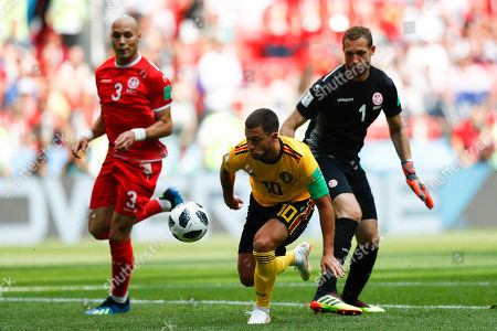 Belgium's Eden Hazard, center, challenges for the ball with Tunisia goalkeeper Farouk Ben Mustapha and Tunisia's Yohan Ben Alouane before scoring his side's fourth goal during the group G match between Belgium and Tunisia at the 2018 soccer World Cup in the Spartak Stadium in Moscow, Russia