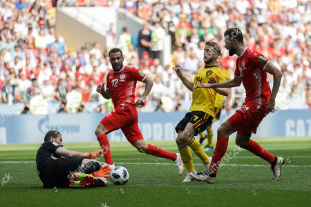 Tunisia goalkeeper Farouk Ben Mustapha, left, stops the ball ahead of Belgium's Dries Mertens, second right, during the group G match between Belgium and Tunisia at the 2018 soccer World Cup in the Spartak Stadium in Moscow, Russia