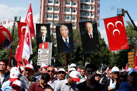 People attend an election rally of the Nationalist Movement Party, or MHP, in Ankara, Turkey, . Posters in the background show, from left to right, the Turkish Republic founder Mustafa Kemal Ataturk, MHP founder Alparslan Turkes and MHP leader Devlet Bahceli. Turkish voters will vote Sunday, June 24, in a historic double election for the presidency and parliament