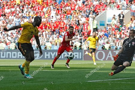 Belgium's Romelu Lukaku, left, scores past Tunisia goalkeeper Farouk Ben Mustapha, right, his team's third goal during the group G match between Belgium and Tunisia at the 2018 soccer World Cup in the Spartak Stadium in Moscow, Russia, . Lukaku scored twice in Belgium's 5-2 victory
