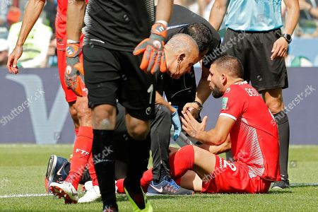 Stock Photo of Tunisia's Syam Ben Youssef, right, is seen by his medical team during the group G match between Belgium and Tunisia at the 2018 soccer World Cup in the Spartak Stadium in Moscow, Russia, . Belgium defeated Tunisia 5-2