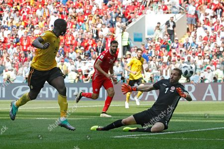 Belgium's Romelu Lukaku, left, scores past Tunisia goalkeeper Farouk Ben Mustapha, right, his team's third goal during the group G match between Belgium and Tunisia at the 2018 soccer World Cup in the Spartak Stadium in Moscow, Russia