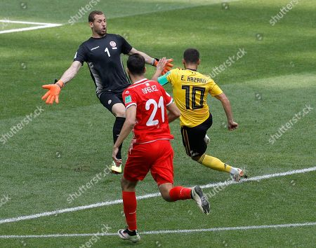 Belgium's Eden Hazard, right, scores his side's fourth goal against Tunisia goalkeeper Farouk Ben Mustapha as Tunisia's Hamdi Naguez tries to block during the group G match between Belgium and Tunisia at the 2018 soccer World Cup in the Spartak Stadium in Moscow, Russia
