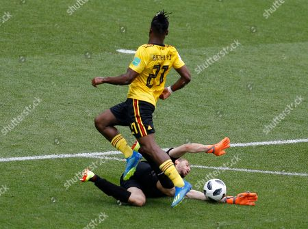 Belgium's Michy Batshuayi, top, jumps over as Tunisia goalkeeper Farouk Ben saves the ball Mustapha during the group G match between Belgium and Tunisia at the 2018 soccer World Cup in the Spartak Stadium in Moscow, Russia