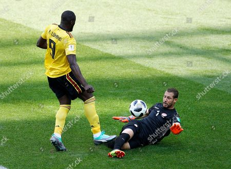 Belgium's Romelu Lukaku, left, tries to score as Tunisia goalkeeper Farouk Ben Mustapha tries to save a ball during the group G match between Belgium and Tunisia at the 2018 soccer World Cup in the Spartak Stadium in Moscow, Russia