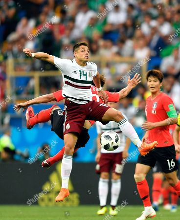 Mexico's Javier Hernandez, front, jumps for the ball with South Korea's Kim Shin-wook during the group F match between Mexico and South Korea at the 2018 soccer World Cup in the Rostov Arena in Rostov-on-Don, Russia