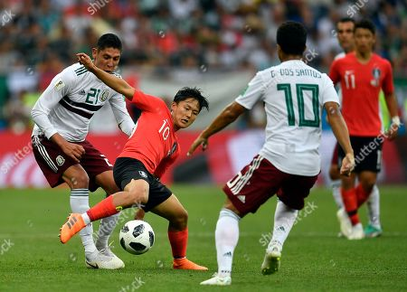 South Korea's Lee Seung-woo, second left, duels for the ball with Mexico's Edson Alvarez, left, during the group F match between Mexico and South Korea at the 2018 soccer World Cup in the Rostov Arena in Rostov-on-Don, Russia