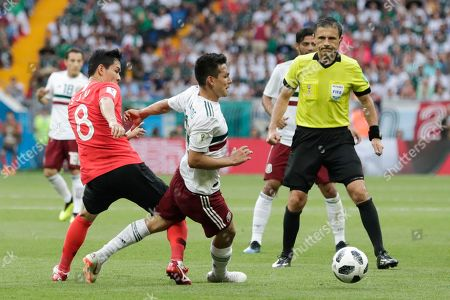 Referee Milorad Mazic from Serbia, right, watches as South Korea's Ju Se-jong, left, and Mexico's Hirving Lozano, fight for the ball during the group F match between Mexico and South Korea at the 2018 soccer World Cup in the Rostov Arena in Rostov-on-Don, Russia