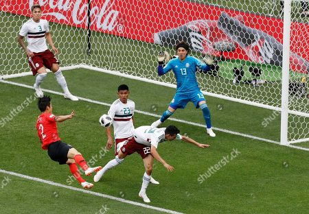 South Korea's Lee Yong, left, takes a shot at goal as Mexico's Hirving Lozano and Jesus Gallardo attempt to block during the group F match between Mexico and South Korea at the 2018 soccer World Cup in the Rostov Arena in Rostov-on-Don, Russia, . Mexico goalkeeper Guillermo Ochoa and teammate Carlos Salcedo watch from goal