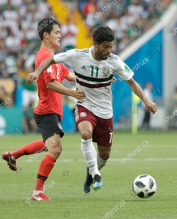 Mexico's Carlos Vela, right, challenges for the ball with South Korea's Ju Se-jong during the group F match between Mexico and South Korea at the 2018 soccer World Cup in the Rostov Arena in Rostov-on-Don, Russia
