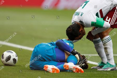 Mexico goalkeeper Guillermo Ochoa, left, lies on the pitch as Mexico's Rafael Marquez checks on him during the group F match between Mexico and South Korea at the 2018 soccer World Cup in the Rostov Arena in Rostov-on-Don, Russia