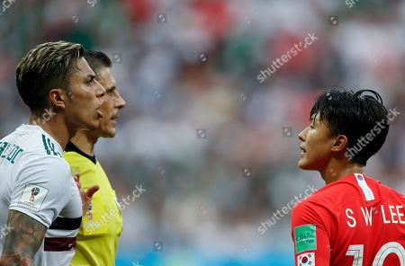 South Korea's Lee Seung-woo, right, looks at Mexico's Carlos Salcedo during the group F match between Mexico and South Korea at the 2018 soccer World Cup in the Rostov Arena in Rostov-on-Don, Russia