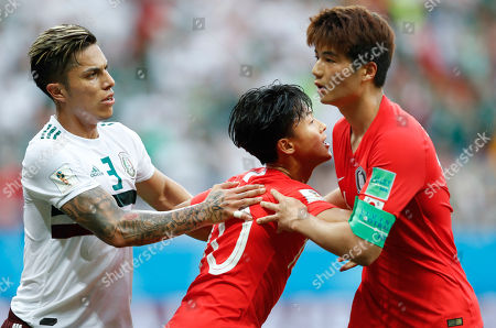 South Korea's Lee Seung-woo, center= hols teammate Ki Sung-yueng as Mexico's Carlos Salcedo stands beside during the group F match between Mexico and South Korea at the 2018 soccer World Cup in the Rostov Arena in Rostov-on-Don, Russia