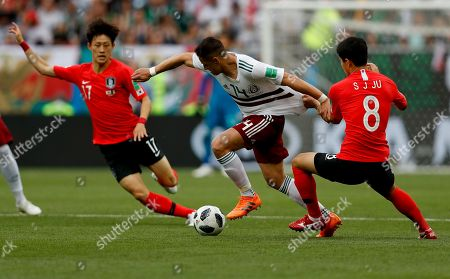 Mexico's Javier Hernandez, center, challenges for the ball with South Korea's Ju Se-jong during the group F match between Mexico and South Korea at the 2018 soccer World Cup in the Rostov Arena in Rostov-on-Don, Russia