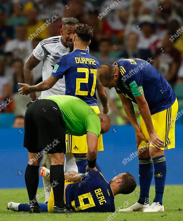 Referee Szymon Marciniak from Poland, bottom left, talks with Sweden's Marcus Berg, on the ground, as Germany's Jerome Boateng, top left, argues with Sweden's Jimmy Durmaz during the group F match between Germany and Sweden at the 2018 soccer World Cup in the Fisht Stadium in Sochi, Russia
