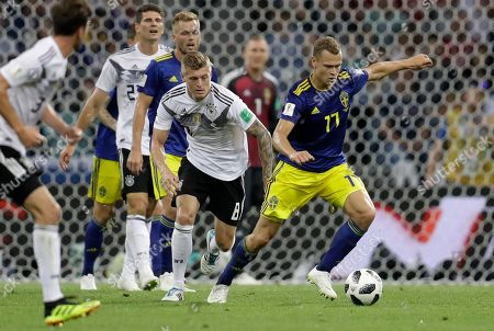 Germany's Toni Kroos, left, and Sweden's John Guidetti challenge for the ball during the group F match between Germany and Sweden at the 2018 soccer World Cup in the Fisht Stadium in Sochi, Russia