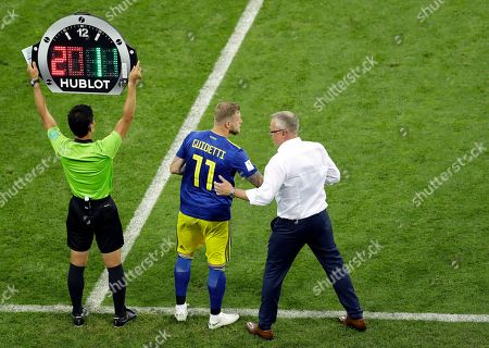 Sweden's head coach Janne Andersson, right, converses with player John Guidetti, middle, as the fourth official Ryuji Sato of Japan, holds up the electronic substitute board during the group F match between Germany and Sweden at the 2018 soccer World Cup in the Fisht Stadium in Sochi, Russia