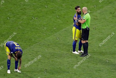 Referee Szymon Marcniak of Poland, right, talks with Sweden's Jimmy Durmaz, middle, at the end the group F match between Germany and Sweden at the 2018 soccer World Cup in the Fisht Stadium in Sochi, Russia